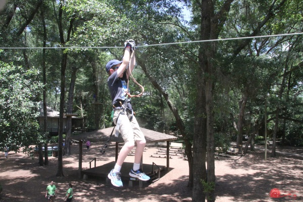 Zip lining on medium course at Tree to Tree Adventures